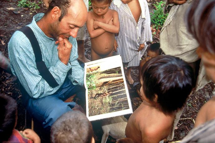 Roberto Pandiani explica conteúdo de um livro para crianças ao seu redor