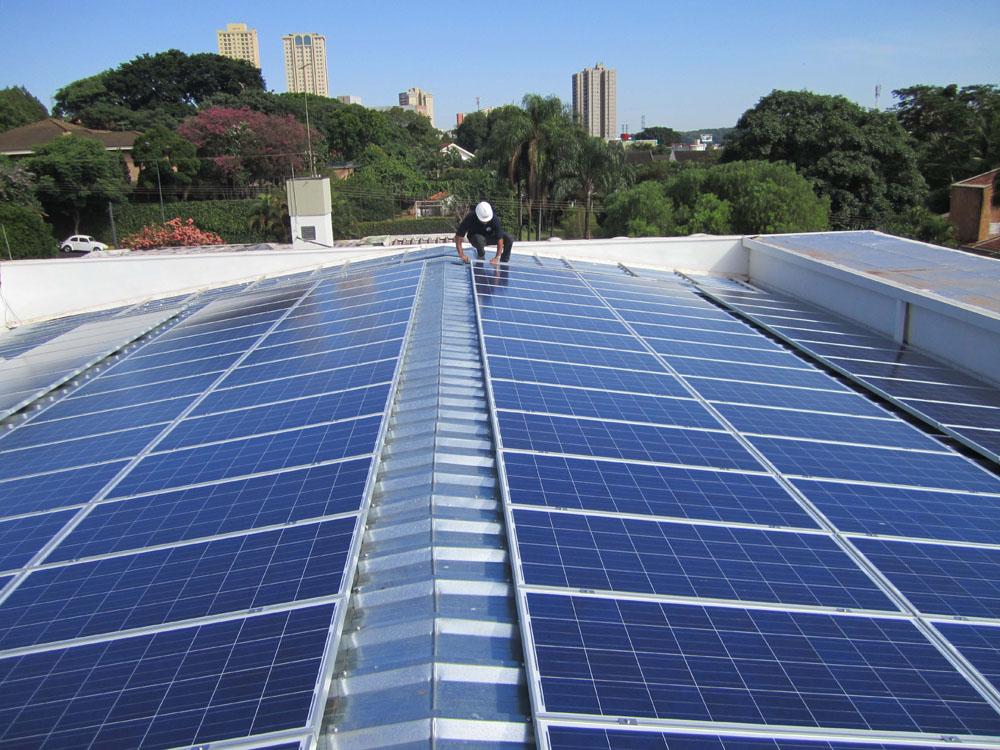 Operário instalando um conjunto de painéis solares em um telhado