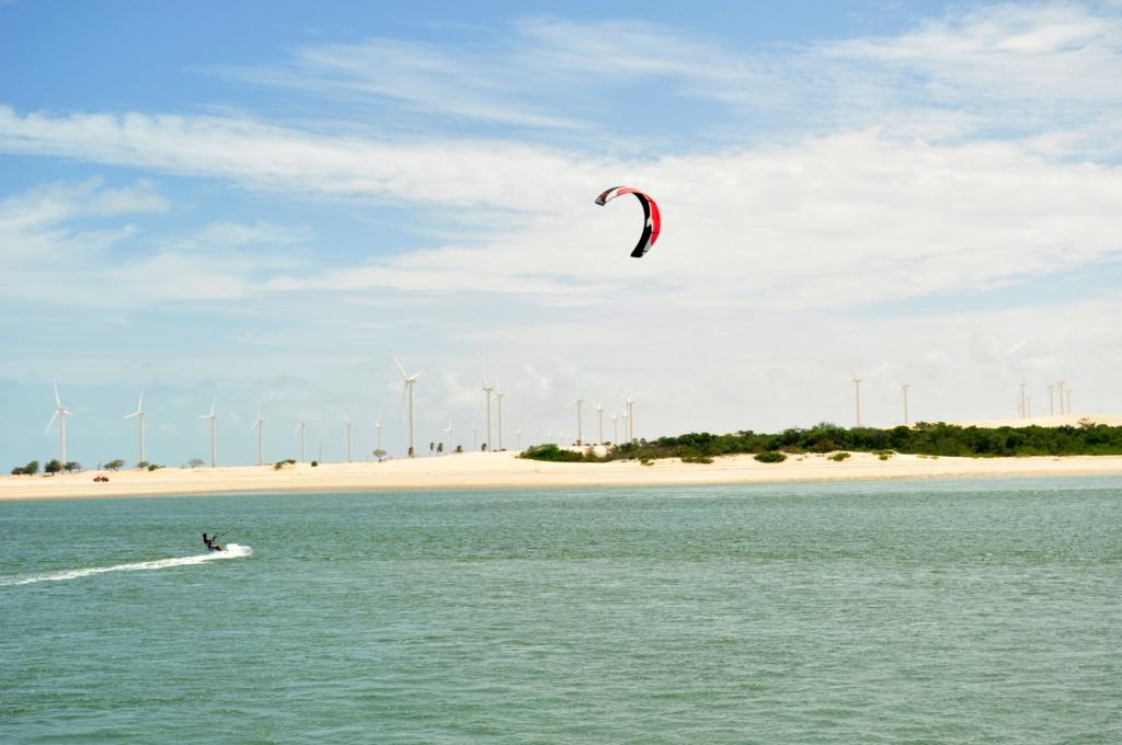 Visão da Praia de Canoa Quebrada, Ceará. Ao fundo, aerogeradores captam vento para gerar eletricidade. No primeiro plano, uma pessoa surfa puxada por um parapent