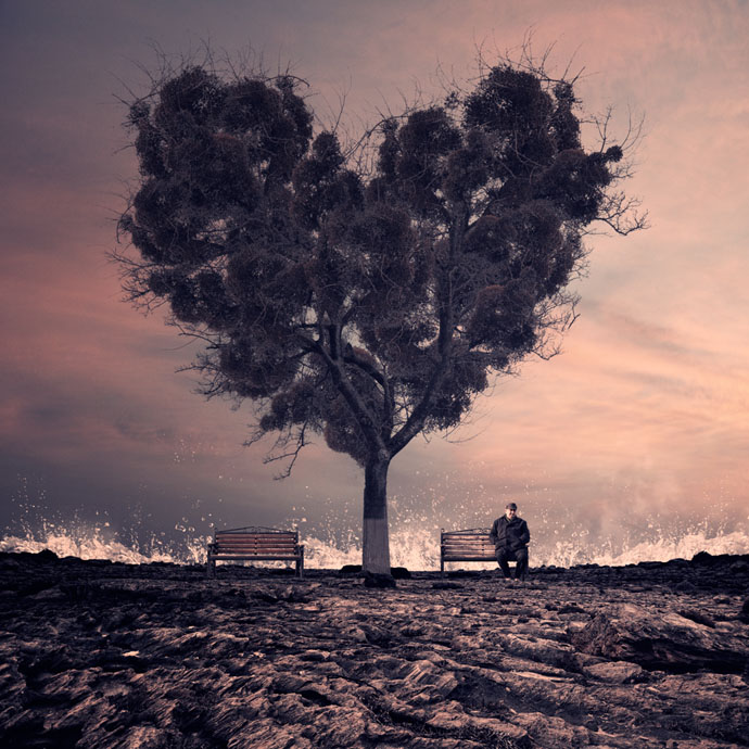 """Obra """"Esperando pelo amor"""", do artista romeno Caras Ionut. Mostra uma homem sentado ao lado direito de uma árvore com a copa em formato de coração. Ao fundo percebem-se ondas do mar batendo na rocha."""