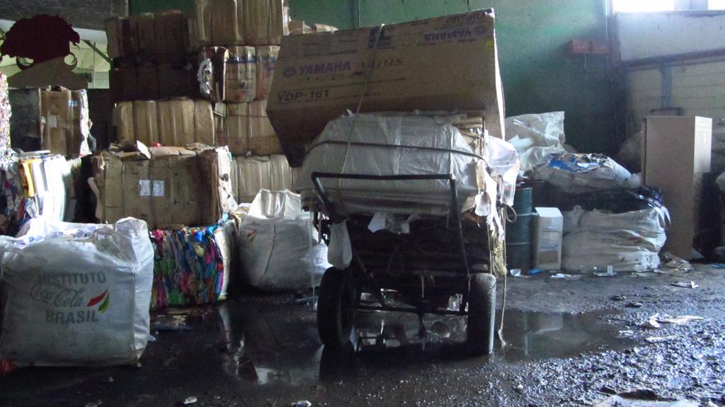 Carroça com carga de papelão aguarda em um galpão de triagem de materiais para reciclagem