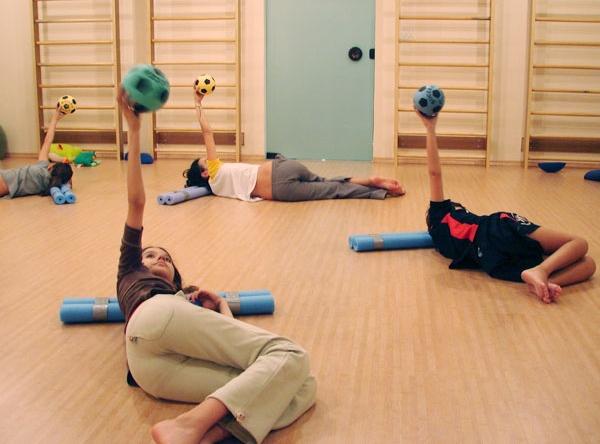 Quatro mulheres executam exercícios com bola em aula de pilates