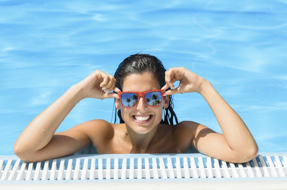 mulher dentro de uma piscina apoiada na borda, sorrindo e segurando os óculos