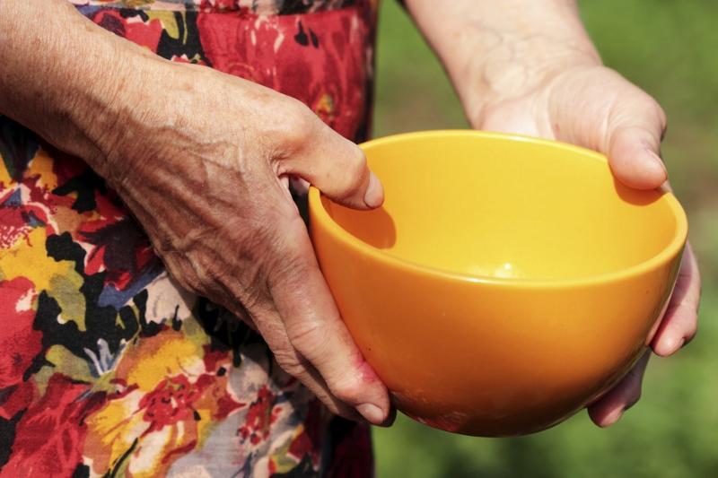 Mulher segura com as suas mãos uma tigela vazia de cor laranja