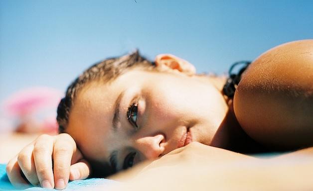 menina deitada na praia tomando sol