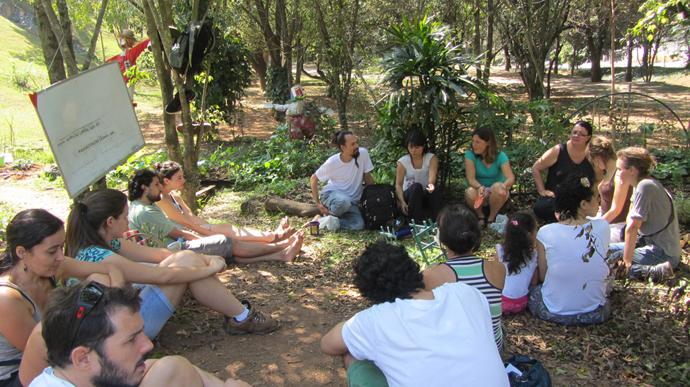 Pessoas reunidas em círculo em um parque discutindo sobre a implantação de hortas urbanas no local