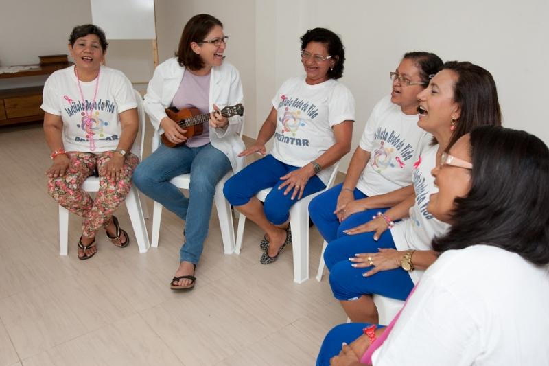 Seis mulheres em tratamento contra o câncer cantam em um roda animadas por Paola Torres, que à esquerda, toca uma cavaquinho