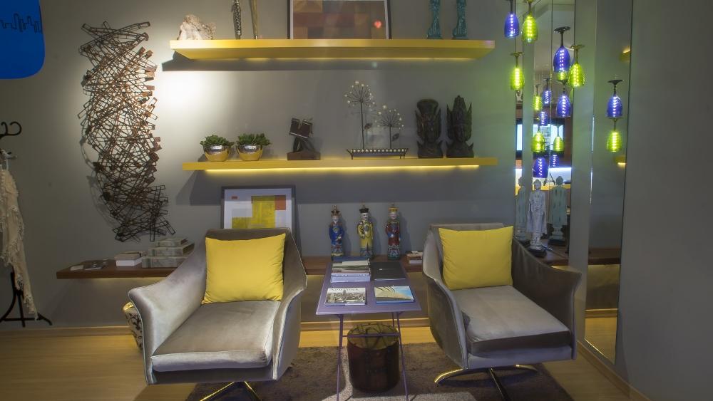 Visão parcial de uma sala com duas cadeira de cor cinza colocadas lado a lado. Entre elas há uma mesa de centro. Ao fundom uma parede cinza com duas prateleiras amarelas