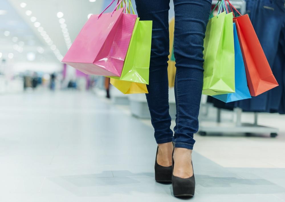 Foto de mulher em uma loja carregando sacolas de compras