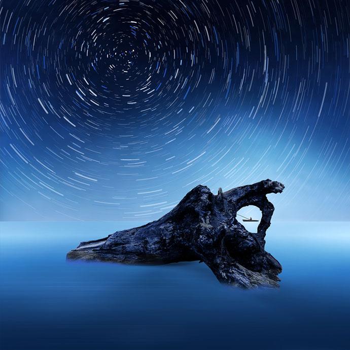 """Obra """"O vigilante"""", do artista romeno Caras Ionut. Mostra um tronco de árvore podre em uma superfície azulada semelhante ao mar. Ao fundo e distante, um homem pesca em uma canoa. Acima, um efeito de rotaçao de estrelas."""