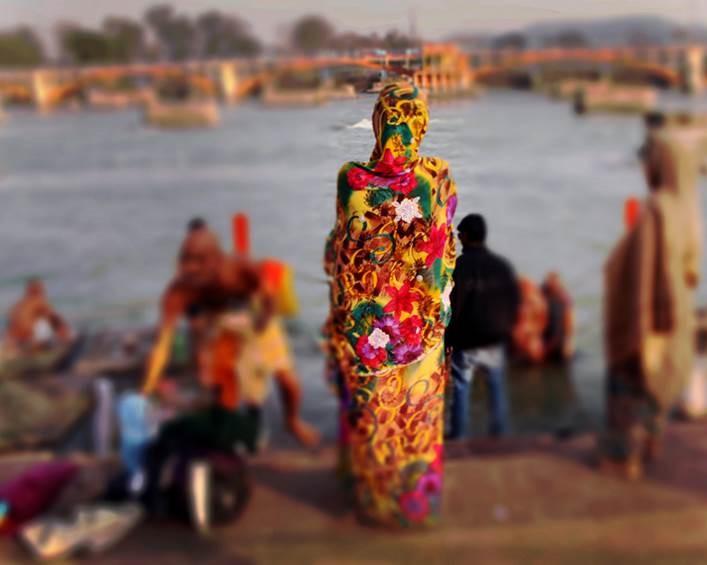 Pessoa indiana de costas com roupa colorida à beira do Rio Ganges