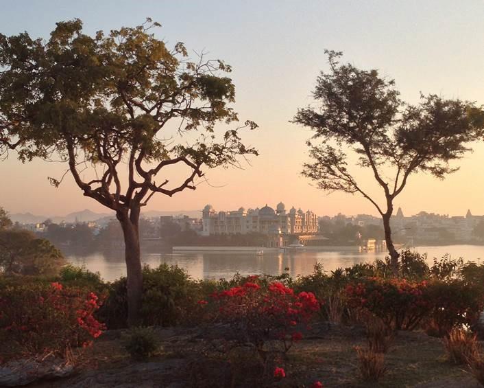 Paisagem da Índia com duas árvores nas extremidades esquerda e direita em primeiro plano com o um rio e edificações ao fundo