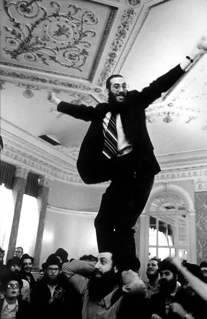 Homem equilibrado nos ombros de um amigo em uma festa judaica em Nova York enquanto os celebrantes observam com apreensão