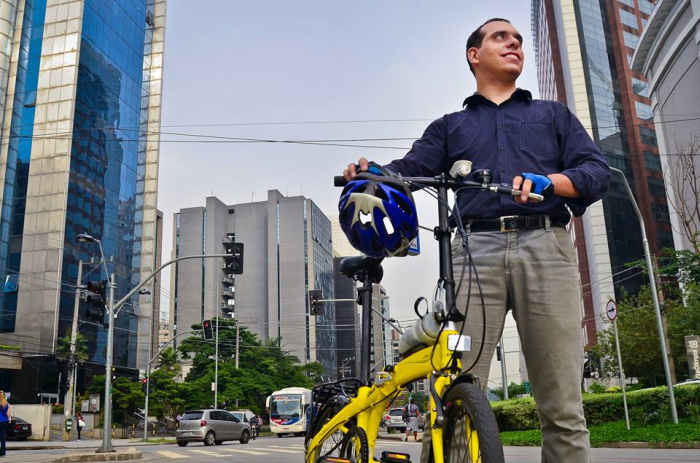 """William Cruz, criador do projeto """"Vá de Bike"""", posa com sua bicicleta indo para o trabalho"""
